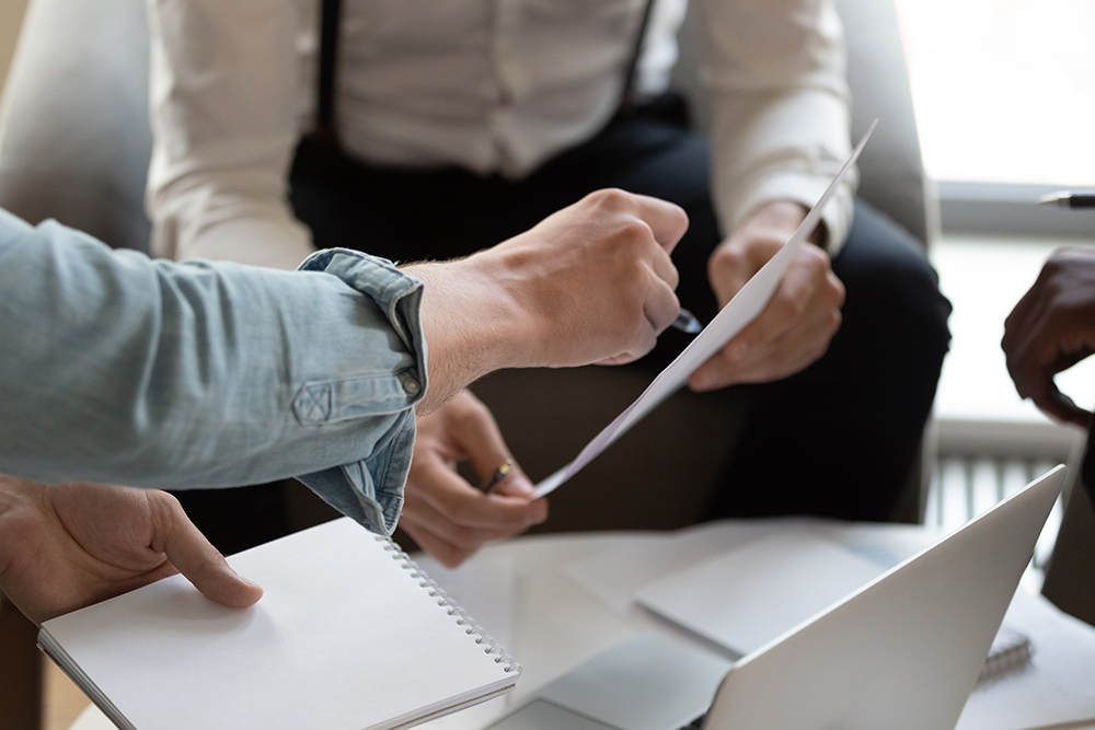 Close up cropped view unrecognizable businesspeople do paperwork during meeting in office, bank worker explain contracts terms conditions to client, discuss credit application, financial deal concept