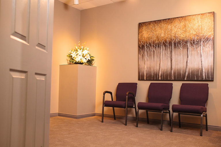 The Viewing room in house at Oliver's Funeral Home. Three chairs, flowers on display, and a photo of trees on the wall