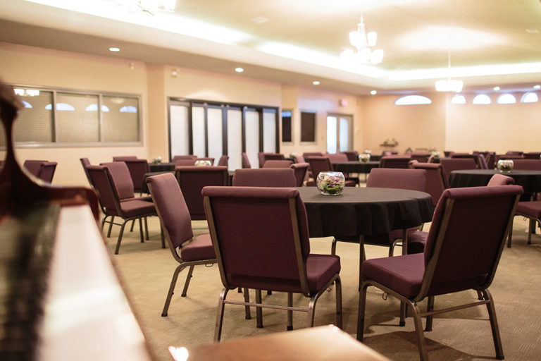 Chapel and Reception Hall on site at Oliver's Funeral Home. Chairs around round tables with round glass vase centerpieces in the center of each table.