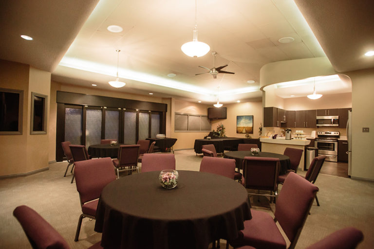 The Tea Room on site at Oliver's Funeral Home. Features round tables with cushioned chairs, a kitchen complete with a microwave, oven, stove, fridge, coffee, and tea.