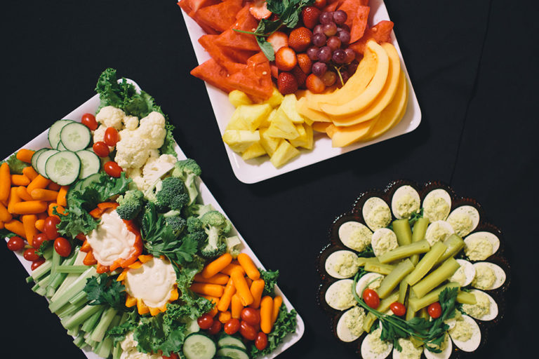 Catering at Oliver's Funeral Home. A vegetable tray with carrots, cucumbers, tomatoes, cauliflower, broccoli, dip, red peppers, orange peppers. A fruit tray with grapes, watermelon, pineapple, and strawberries. A tray of deviled eggs and celery.