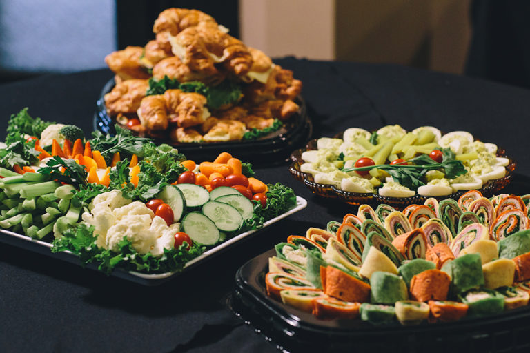 Catering on site at Oliver's Funeral Home. A vegetable plate consisting of cucumbers, carrots, tomatoes, orange peppers, red peppers, celery. Ham and cheese rollups. Devilled eggs. Croissant sandwiches with meat and cheese.
